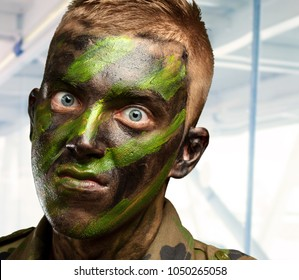 closeup of angry soldier with painting, indoor