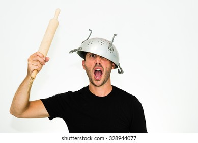 close-up of angry young caucasian man with a colander on his head and rolling pin on his hand looking and screaming at you - isolated on white background