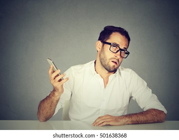 Closeup annoyed young man with cellphone. Long wait times, horrible conversations concept. Human emotion face expression reaction
