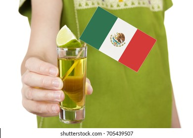 Close-up of anonymous woman in traditional Mexican outwear holding shot of tequila with Mexican flag.