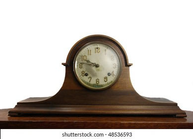 Closeup of an antique mantel clock on wooden mantel against a plain white background.