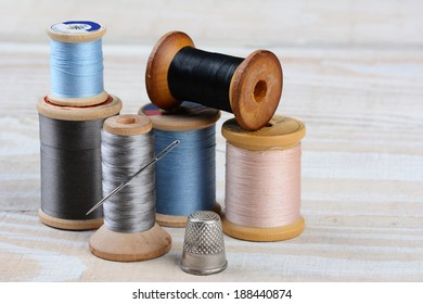 Closeup of antique spools of thread with a needle and thimble on a rustic wooden table. Horizontal format