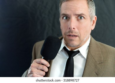 Close-up of an anxious man speaking into microphone.