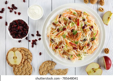 close-up of Apple Cranberry and walnuts Coleslaw salad on a white plate on wooden table with red apple, multigrain crispbread  and greek yogurt dressing at background, view from above
