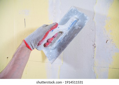 A close-up of applying gypsum finish, plaster on a wall with a stainless steel trowel. Renovation of a house, a flat with a professional construction team.