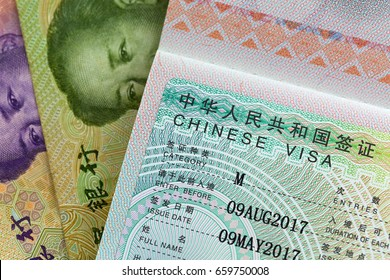 Closeup of approved China Business Visa on Chinese currency banknotes money