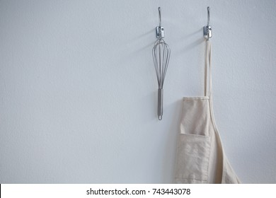 Close-up of apron and whisker hanging on hook