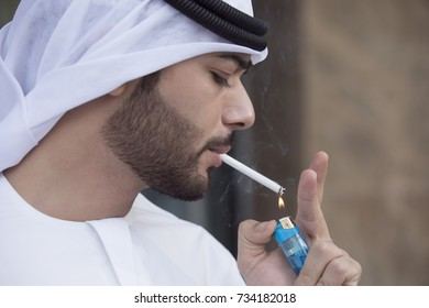 Close-up of a Arab young man wearing kandoura and agal, lighting a cigarette.
