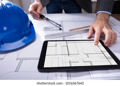 Architects scale images stock photos vectors shutterstock close up of architects hand using digital tablet with blueprint on desk malvernweather Image collections