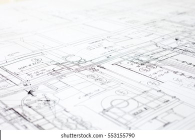 A close-up of an architectural blue print with black and white details, marked by measurements and construction and design details.
