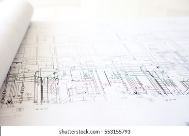 A close-up of an architectural blue print with black and white details, marked by measurements and construction and design details, and rolled on one side.