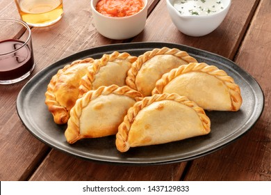 A closeup of Argentinian empanadas with sauces and wine on a dark rustic wooden background