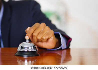 Closeup arm of man wearing blue suit pressing desk bell at hotel reception