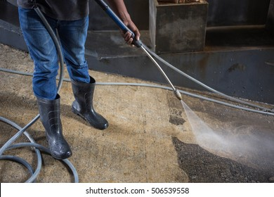 Nahaufnahme eines Mannes, der Hochdruckwasserpistole-Reinigungsböden hält.