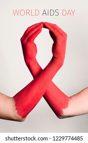 closeup of the arms of two men painted red forming a red awareness ribbon and the text world aids day against an off-white background
