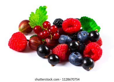 Close-up arrangement mixed, assorted berries including blackberries, strawberry, blueberry, raspberries and fresh leaf on white
