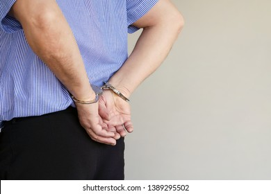 Close-up. Arrested elderly man handcuffed hands isolated on gray background. Prisoner or arrested terrorist, close-up of hands in handcuffs. Close-up view