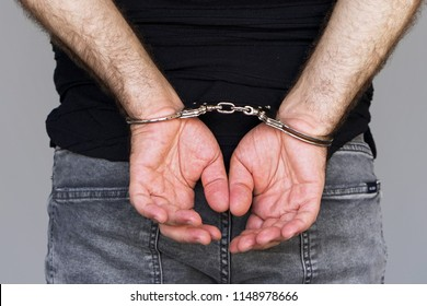 Close-up. Arrested man handcuffed hands isolated on gray background. Prisoner or arrested , close-up of hands in handcuffs.