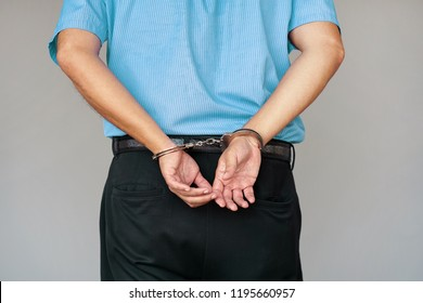 Close-up. Arrested man handcuffed hands at the back. Isolated on gray background. Businessman in office in handcuffs holding a bribe. Arrested man in handcuffs. Criminal hands locked in handcuffs.