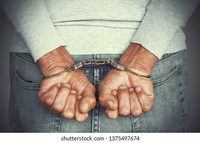 Close-up. Arrested man handcuffed hands isolated on gray background. Prisoner or arrested terrorist, close-up of hands in handcuffs. Toning