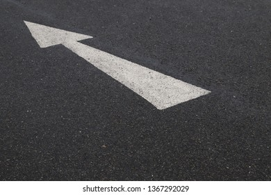 Closeup of arrow on asphalt ground of the parking lot after raining. The traffic sign show the symbol of safty and right direction to the goal.