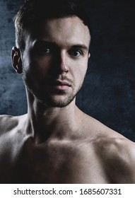 Close-up art portrait of unshaven brutal Caucasian man looking at the camera. Muscular undressed sexy handsome model posing on dark background