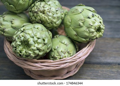 closeup of artichokes in a tray on a rustic wooden table