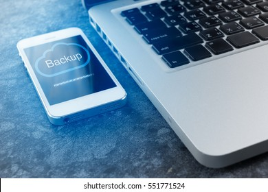 close-up Artificial Intelligence mobile phone that is Cloud Backup Storage from laptop computer.business data online backup,connection network security,hi-speed information transfer concept.