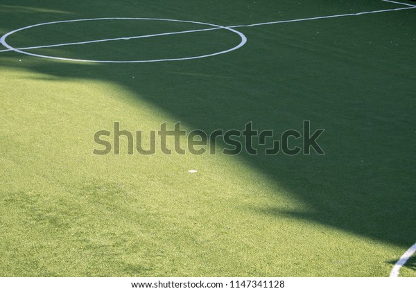 Close-up of artificial turf. Blurred legs of soccer players in the background.