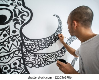 Closeup artist painting abstract pattern in octopus shape on white cement wall. acrylic color.