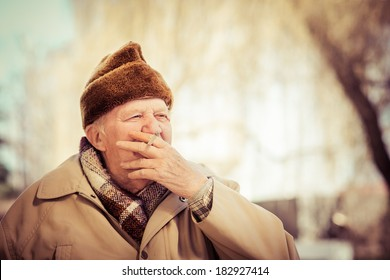Closeup artistic photo of senior man smoking