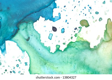 Closeup of artist's watercolor palette with green and blue paint splashes