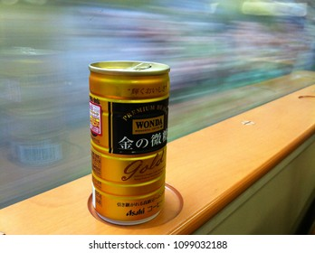 """Closeup of Asahi """"Wonda"""" canned golden premium coffee with less sugar, inside the Shinkansen train of Japan with fast speed background"""