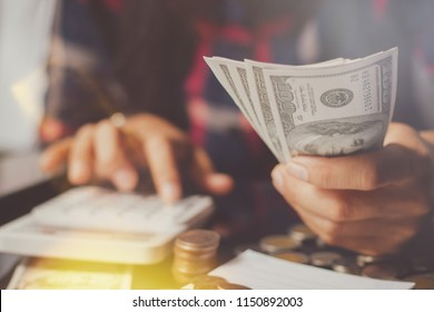 closeup of Asia   business,workingwoman ,people holding Us dollar banknotes money ,using calculator calculate  money with happy in office.