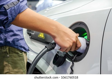 Close-up asia men hands who are fueling a new vehicle electrification via rechargeable electricity machine, Electric cars are a new innovation in the future, built to replace cars powered by oil.