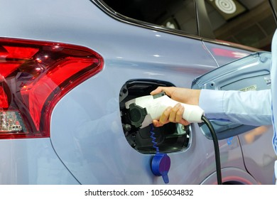 Close-up asia women hands who are fueling a new vehicle electrification via rechargeable electricity machine, Electric cars are a new innovation in the future, built to replace cars powered by oil.