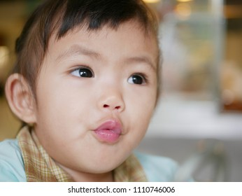 Closeup of Asian baby girl, 15 months old, puckering her lips up - baby's development through mimicking other people's facial expressions