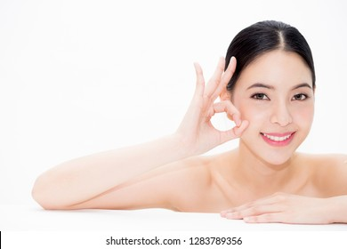 Close-up of Asian beautiful healthy smiling woman in beauty skincare concept with ok sign hand gesture isolated over white background