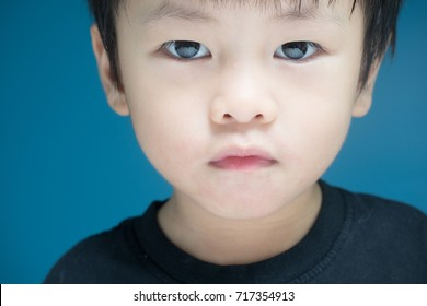 Close-up of asian boy face with round eyes, adorable, thinking for playing idea