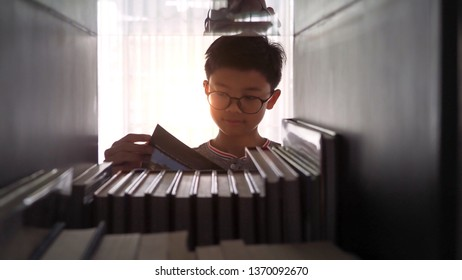 Closeup of an Asian boy wearing a glasses reading a book at home. A see through view from the book shelve with orange sunlight in the background. Selected focus.