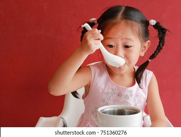 Close-up asian child girl eating pork bone soup on high chair against red wall background at chinese restaurant.