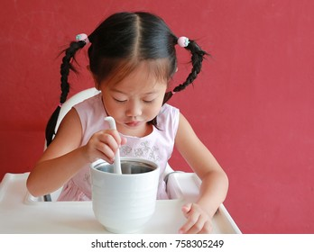 Close-up asian child girl eating pork bone soup on high chair against red wall background