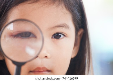 Closeup of asian child girl eye swell from bacteria virus looking through a magnifying glass
