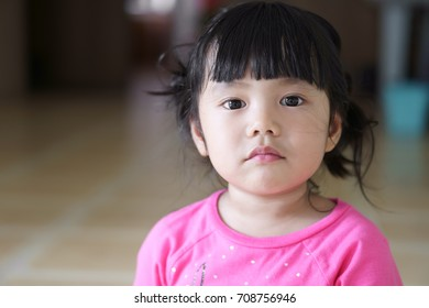 closeup Asian children cute or kid girl and big eye with look at the face and displeased or frown angry at home with space