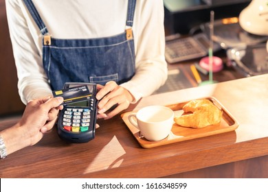 Close-up of asian customer using his credit card with contactless nfs technology to pay a barista for his coffee purchase at a cafe bar.