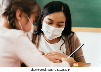 Close-up of Asian female teacher wearing a face mask in school building tutoring a primary student girl. Elementary pupil is writing and learning in classroom. Covid-19 school reopen concept