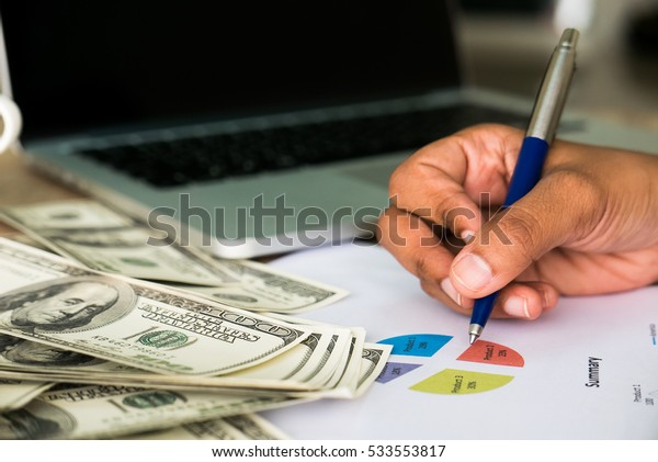 Closeup of Asian female writes something on business charts under bunch of dollars banknotes nearby her labtop for business, finance, tax and people concept