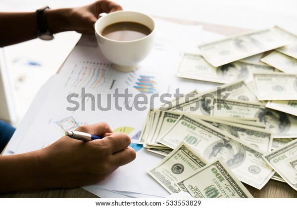 Closeup of Asian female writes something on business charts under bunch of dollars banknotes nearby her labtop and a cop of coffee for business, finance, tax and people concept
