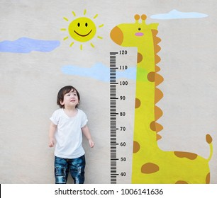 Closeup asian kid stand for measure height and look at cute giraffe cartoon at the marble stone wall textured background