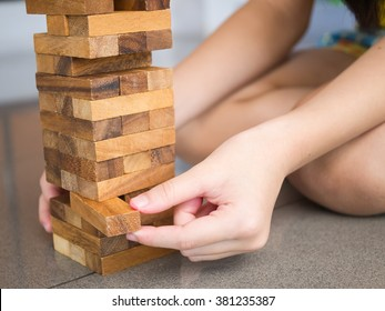 Closeup of Asian kid's hand playing wood blocks stack game